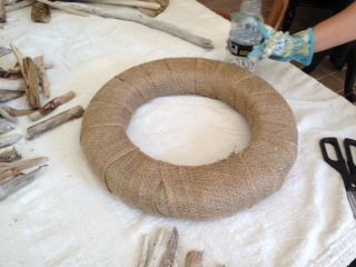 The 1st step in making a driftwood wreath, wrap your foam wreath form in burlap.