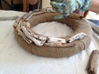2nd step in making a DIY driftwood wreath, adhere pieces of driftwood to the burlap covered foam wreath form.  Add pieces in an off set pattern around the wreath.