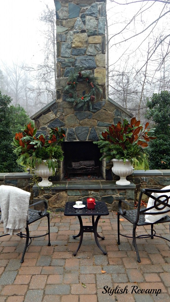 Decorating and outdoor fireplace with fresh clipping in a planter and a fresh cut wreath.