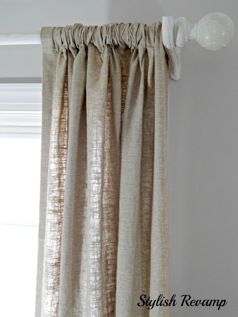 DIY curtain rods against a cool beige/grey paint