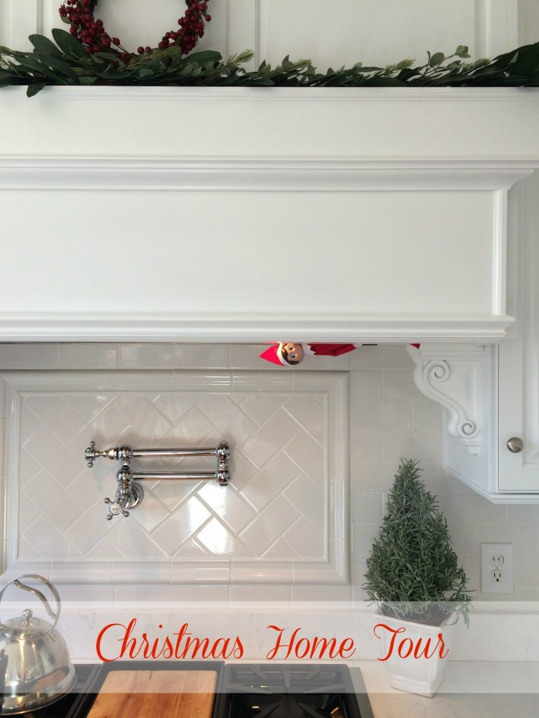 White kitchen with white subway tile and a pot filler with the elf on the shelf peeking out.