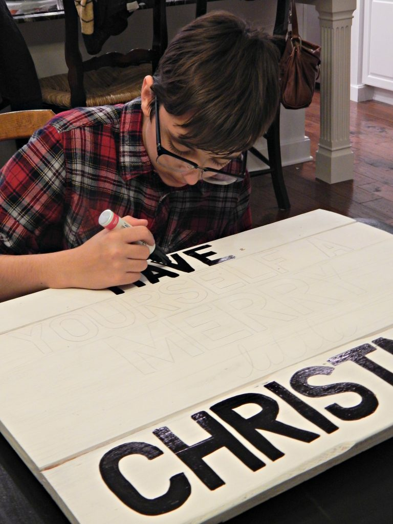 Hand painting DIY Christmas signs using Sharpie paint pens.