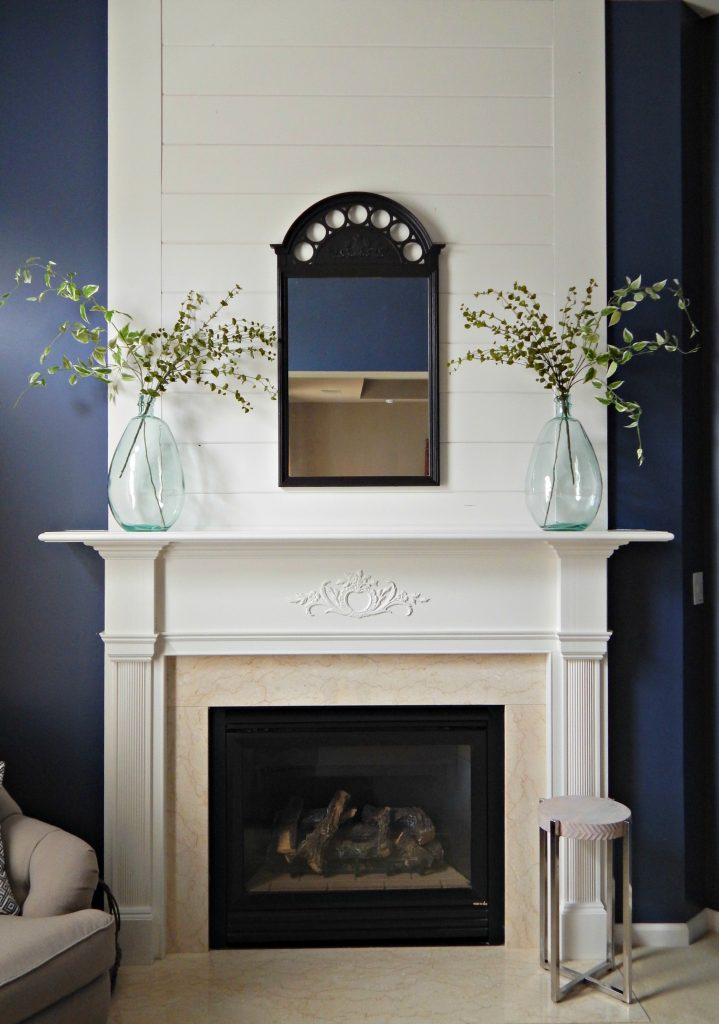 Shiplap fireplace with faux greenery in glass jars