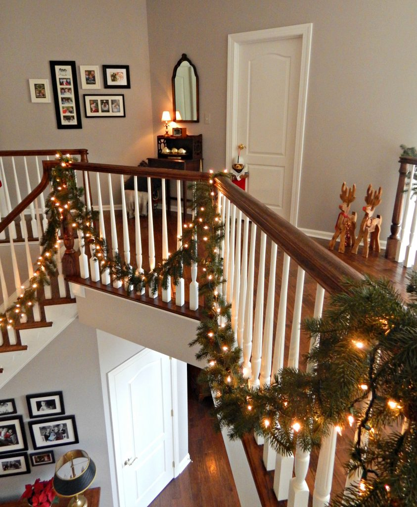 Banisters draped in garland with DIY Reindeers waiting for takeoff.