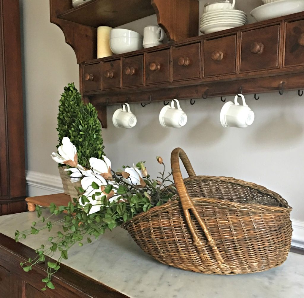 Goodwill Basket with sprigs of greenery and Magnolia Branches